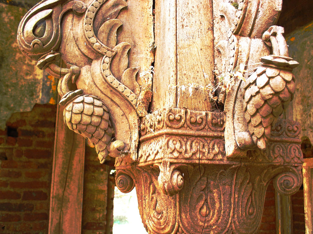 Carved wooden beam in the ruins of old palace at